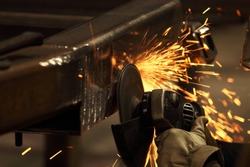A metal worker grinds away welded  metal spatter and cleans the surface of a welded surface, causing a spray of sparks.