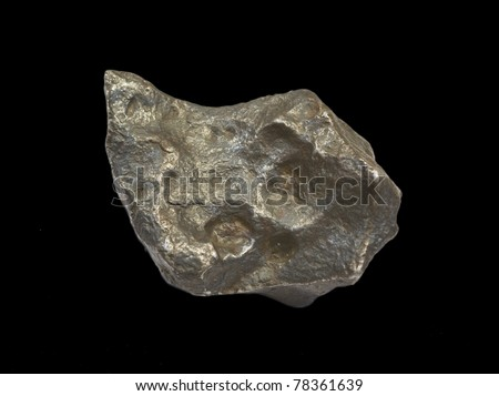 A metallic iron meteorite isolated on black. About 6 cm long.
