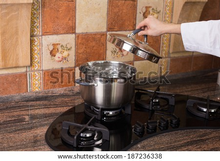 A metallic pan of boiling water on a modern gas cooker