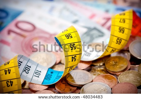 A metaphorical image of a measuring tape on Euro notes and coins - stock photo