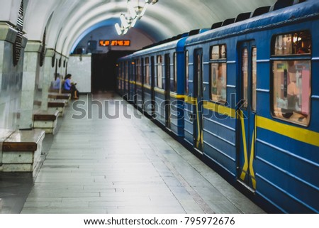 A metro or underground train in blue and yellow color is departing a metro station in Kiev, Ukraine. One passenger is seen on the platform.