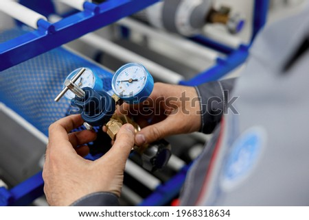 A metrology laboratory specialist takes a compressed gas cylinder for testing and verification. The man connects the pressure gauge. Analyze gas and check connections for leaks.