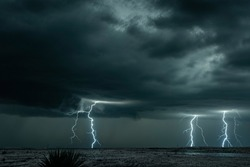 A mezocyclone lightning storm with dark clouds forming over the plains in Tornado Alley, Oklahoma at night