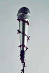 a microphone encircled by a red barbed wire, depicting the idea of the repression of the mass media or the lack of the freedom of speech