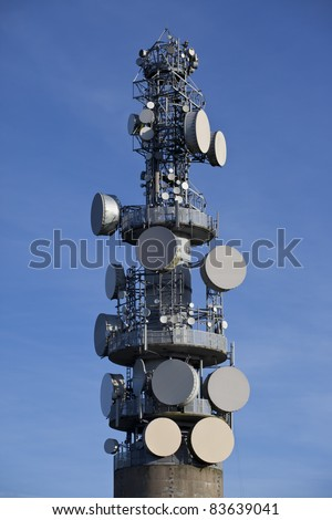 A microwave communications tower covered with dishes