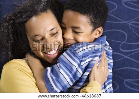 A mid adult African American woman affectionately hugging her young son. Horizontal shot.