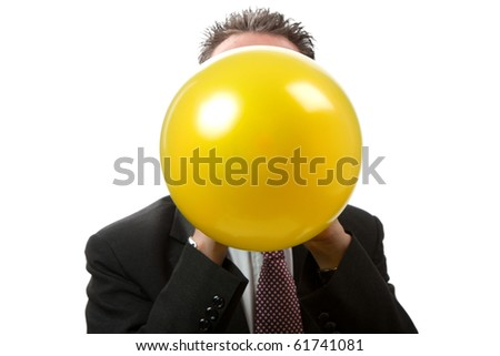 A mid thirties business man blowing up a yellow balloon.  Facing camera.   Studio isolated on a white background.