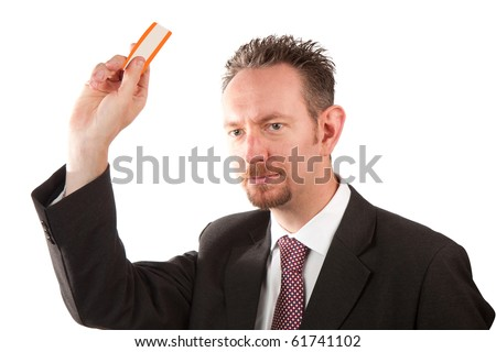 A mid thirties business man holding up a ticket.  The man is wearing a suit and tie and has spiky hair and a goatee beard.  Studio isolated on a white background.