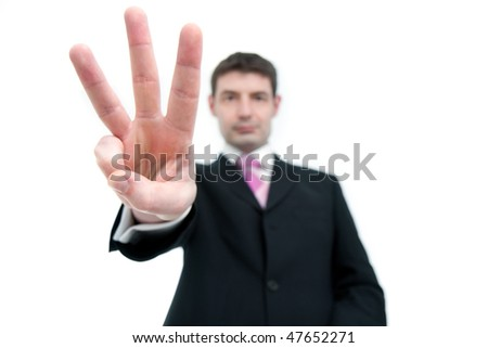 A mid thirties businessman in a black suit holding up three fingers.  Differential focus on the hand. - stock photo