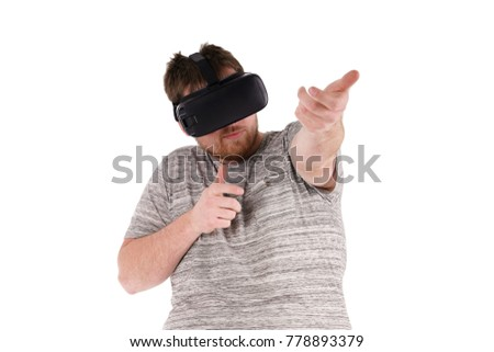 A mid twenties male in a grey stripped t-shirt using a Virtual Reality headset on a white background #778893379