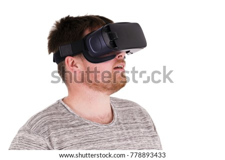 A mid twenties male in a grey stripped t-shirt using a Virtual Reality headset on a white background #778893433