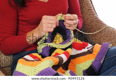 A midaged woman knitting with colorful wool