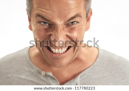 A middle age adult man is very angry about something .show teeth. Picture is toned and made in the dragan effect