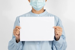 A  Middle age asian woman wearing a medical face mask, holding an empty card, blank space template. Encourage health care from Covid 19 Corona virus, on white background.