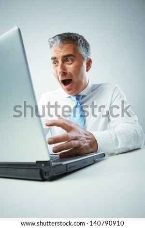A middle age businessman gets shocked from view of laptop