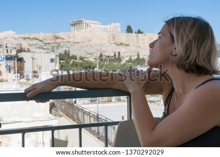 A middle age European woman on the balcony on the background of Acropolis and Parthenon. Athens, Greece.