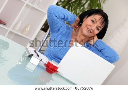 A middle age woman stretching in front of her computer.