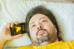 A middle-aged bearded man lies on a pillow in the early morning with his hand holding a phone with an alarm on and an indifferent facial expression. Concept - apathy, doom, depression