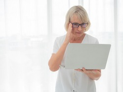 A middle-aged businesswoman is interested in information on a computer monitor while standing in the bedroom. work at home concept