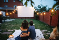 A middle-aged couple in love is watching a movie, in the twilight, outside on the lawn in their courtyard. They are sitting on a tablecloth, watching a projector screen. Man is hugging his wife.