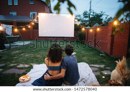 A middle-aged couple in love is watching a movie, in the twilight, outside on the lawn in their courtyard. They are sitting on a tablecloth, watching a projector screen. Man is hugging his wife. Foto stock ©