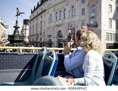 A middle-aged couple sitting on a sightseeing bus, taking photographs