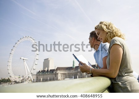 A middle-aged couple standing near the London Eye, looking at a guidebook