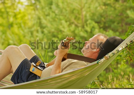 A middle aged man composing music with a guitar and hand held recording device in a hammock in the shade in the summer.
