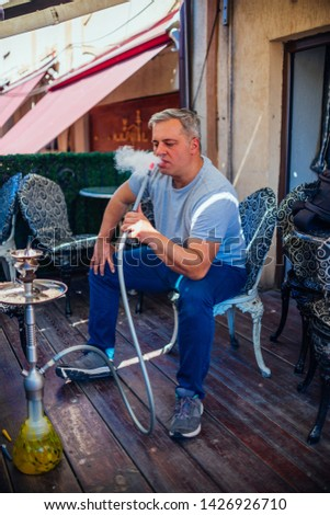 A middle-aged man dressed casually is smoking hookah (shisha) while sitting at an old wooden balcony looking extremely relaxed. #1426926710