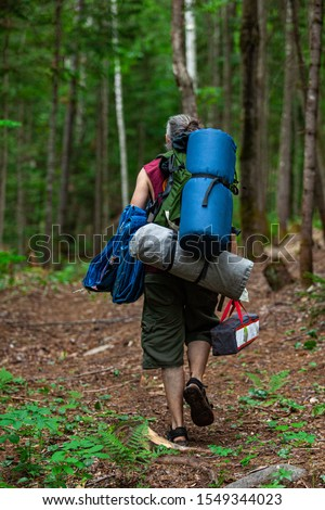 A middle aged man is seen walking through dense woodland carrying backpacks, a tent and camping equipment, seeking a scared ground for mindful retreat. #1549344023