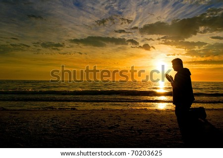 A middle aged man kneeling and praying at the beach with a glorious sunset in the background.