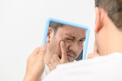 A middle-aged man looking in the mirror and worried about blemishes and wrinkles on his face on white background, Health care concept
