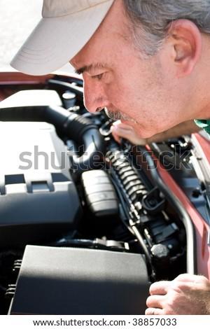 A middle aged man looking under the hood of a car.