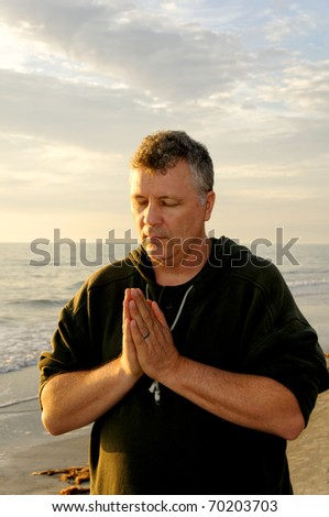 A middle-aged man praying at the ocean in evening light.