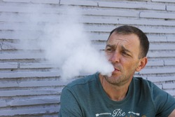 A middle-aged man sitting on a background of gray brick wall and releases the smoke out of her mouth/ Portrait of a man who smokes/ Man blows smoke