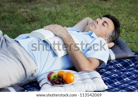 A middle aged man snoozing in the park