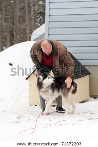 A middle aged man stops to pet a neglected Shepard husky mix dog on a native reservation after delivering a donated dog house to him.