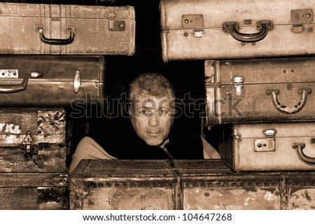 A middle aged man surrounded by sepia toned antique suitcases.