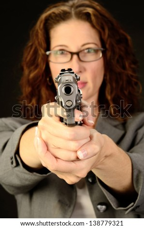A middle aged, white, female business woman or teacher holds a semi automatic pistol during this dark photo shoot against black