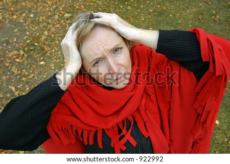 a middle-aged woman keeping her hands on her head and having headache or some problems.