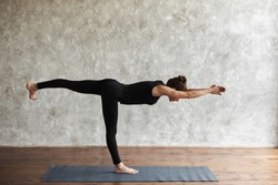 A middle-aged woman practicing yoga, doing Warrior III exercise, Virabhadrasana 3 pose, working out, wearing sportswear, black pants and shirt, indoor full length, side view. Advertising space