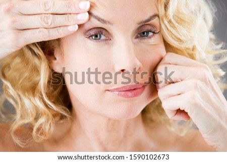 A middle-aged woman pulling the skin on her face