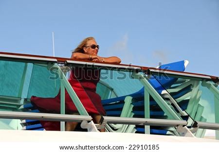 A middle-aged woman sits on the top deck of a cruise ship
