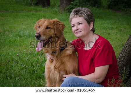 A middle-aged woman sits serenely with her golden retriever, both looking into the distance