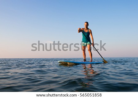 A middle-aged woman stand up paddle boards on a bay at sunset in Ontario, Canada. #565051858