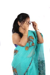 A middleaged Indian woman with eyesight problem wearing her glasses, on white studio background.