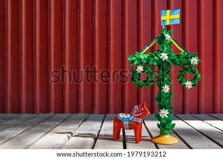 A midsummer pole with flag and Dala horse against red wooden wall. Handmade maypole decorated with flowers for celebrating midsummer day. Kort Glad Midsommar in Swedish or Card Happy Midsummer in eng. Сток-фото ©
