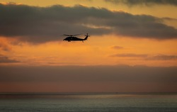 A military helicopter flying toward the left with a cloudy sunset over the pacific ocean