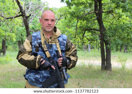 A military man hunter is standing with a firearm in the forest. Hunting season. #1137782123