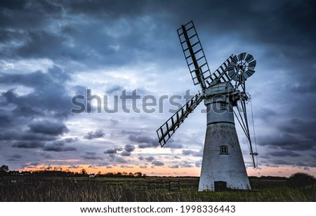 A mill in a field against the background of sunset. Sunset mill view. Windmill at sunset. Sunset windmill scene